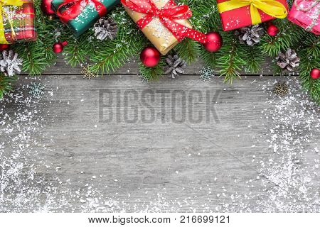 Christmas background with fir branches red balls gift boxes and pine cones on rustic wooden table covered with snow. Flat lay. top view with copy space