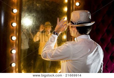 retro young man looks at himself in mirror