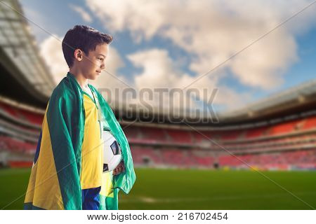 Concept of Brazilian soccer / Portrait of boy holding a ball and wrapped up in Brazilian flag.