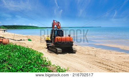 Excavator or digger moving beach sand after erosion on a tropical beach with calm ocean in Cairns Queensland Australia
