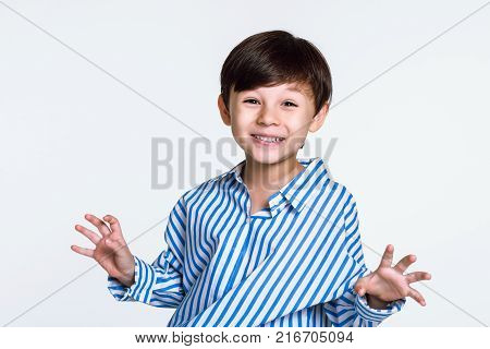 Studio portrait of a boy staring at the camera and acting up
