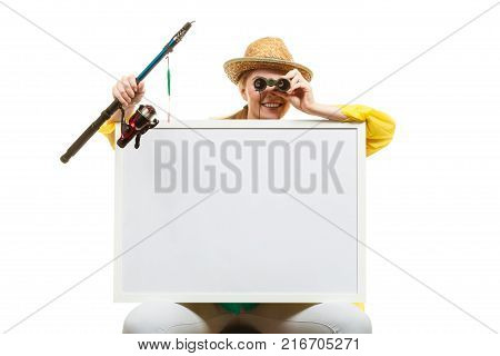Fishery spinning equipment angling sport and activity concept. Happy woman with fishing rod and binoculars holding blank white board with copyspace.