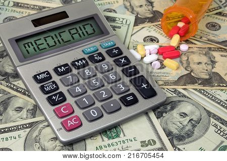 medicaid text sign on calculator with pills and bottle on paper money