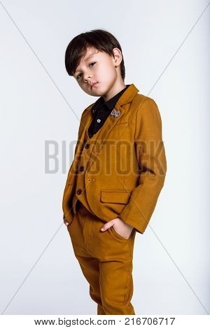 Studio portrait of a boy staring at the camera in a wonderful pose, Casual suit