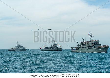Pattaya Thailand - November 9 2017 Navy warships running on sea while warplanes flying above warships on the 50th anniversary ASEAN international fleet review 2017 drill in Pattaya Thailand