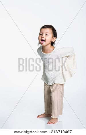 Studio portrait of a young girl hiding something and making fun of an opponent