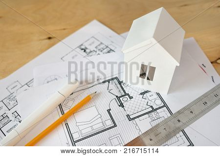 House remodel. The top view of a table of architects with the drawing of the house, with the paper model of the house, with a ruler and a pencil.