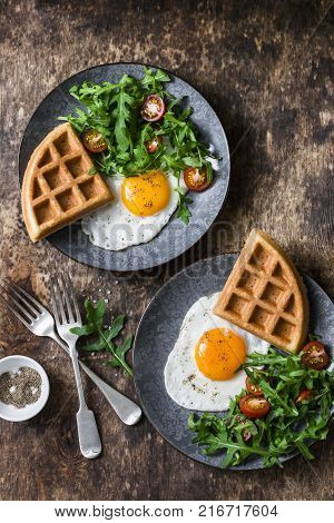 Savory waffles fried eggs and arugula cherry tomato salad - delicious healthy breakfast on wooden background top view