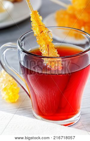 Crystallized sugar is the traditional eastern sweetness of the alarm. Sugar candy in a glass with tea. Ingredients for tea ritual in the countries of Asia and the Middle East. Closeup