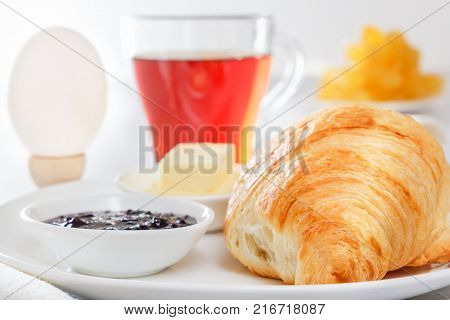 Croissant, boiled egg, tea, butter, jam. Continental French breakfast. Lightings light