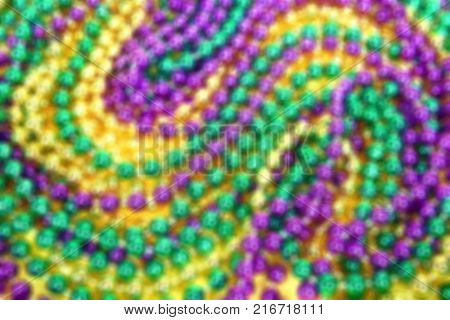 Blurred background of colorful Mardi Gras beads