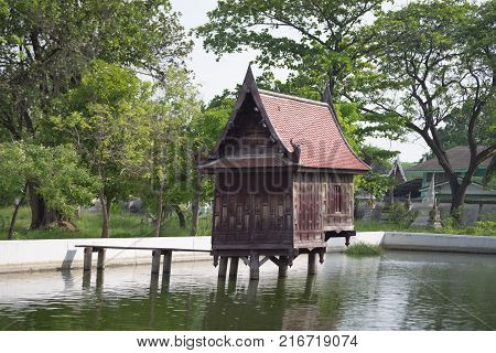 Old wooden house in the pond at Wat Yai Suwannaram Phetchaburi Thailand. It was an old library for the collection of buddhist scriptures.