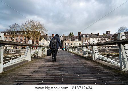 Cork, Ireland - November 12, 2017: Beggar holding a musical instrument crossing a bridge in Cork