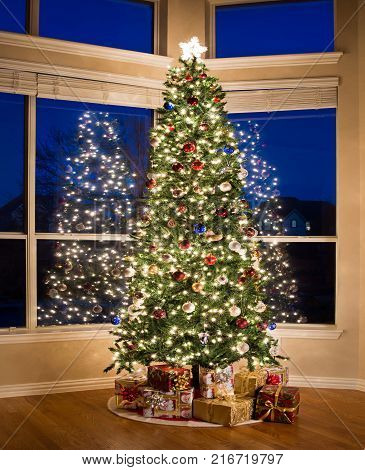 Christmas tree lit up and gifts under the tree