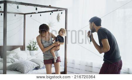 Happy family and little cute daughter dancing near bed in bedroom while famter singing at home in the morning