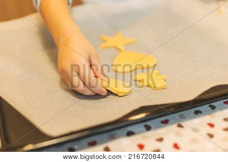 Close up cookies on backing tray ready for cook. Cute chef boy placing Christmas cookies on baking sheet. Kid hand aranging raw biscuits.