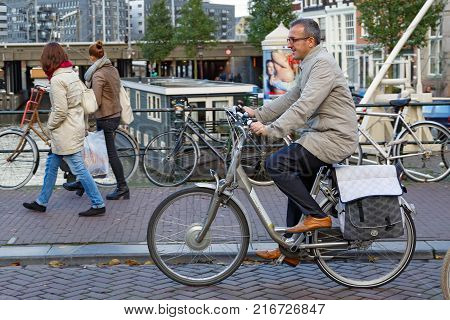 AMSTERDAM/ NETHERLANDS - OCTOBER 22, 2014. A well-dressed man on a bicycle on the Eenhoornsluis bridge over the Princengrach canal.  Amsterdam, the Netherlands.