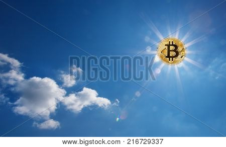 Golden bitcoin glowing in the blue sky instead of the sun. Bitcoin with divergent rays in the sky. The concept of the onset of the bitcoin era.