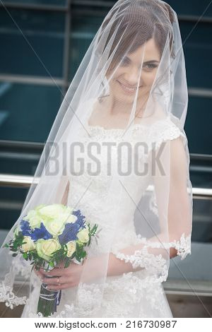 Slender young bride in stylish white dress and veil with wedding bouquet waiting for groom against the backdrop of the architecture of the city. concept of a attractive bride