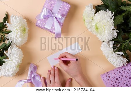 woman hand writing a note with the text thank you on a paper, over beige table and flowers