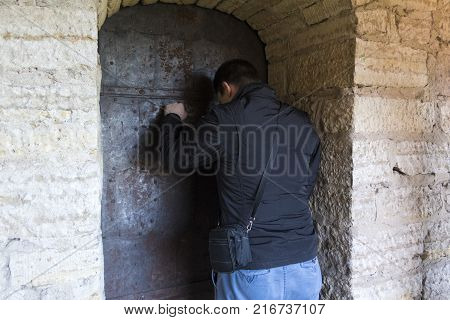 a man knocks on the iron door in the Old Fortress