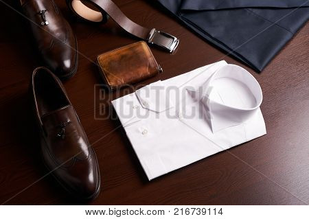 Set of mans fashion and accessories, brown leather shoes, purse, belt, white shirt and dark trousers on wooden background, top view.
