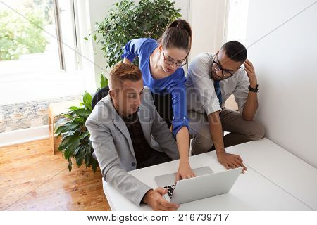Business researchers analyzing market together using internet on laptop in office. Concentrated analysts looking through online document or taking statistics. Technology concept