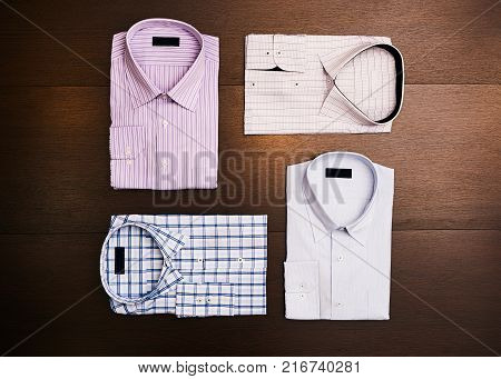 A set of 4 men's shirts on wooden background, top view. Men's fashion
