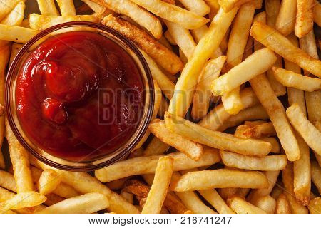 Delicious french fries and ketchup - fast food background top view closeup
