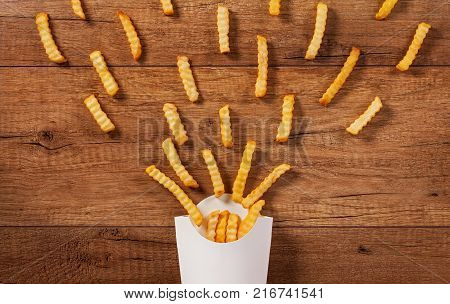 French fries spreading out of a paper holder bag - fast food on brown wooden table
