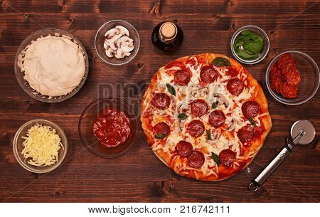 Fresh baked pizza with all the ingredients on the table - top view