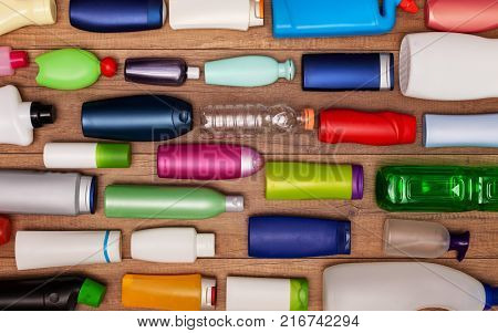 Colorful plastic bottles on wooden surface - the background of pollution
