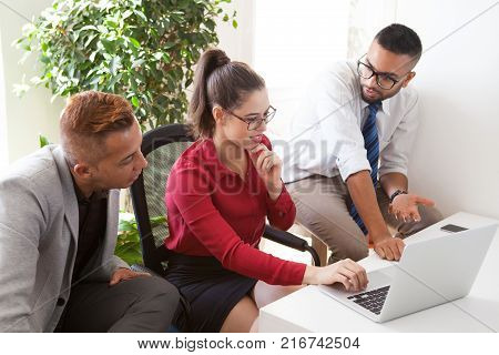 Sophisticated colleagues elaborating marketing strategy in office. Confident Hispanic employee explaining idea of project while business people watching presentation on laptop. Teamwork concept