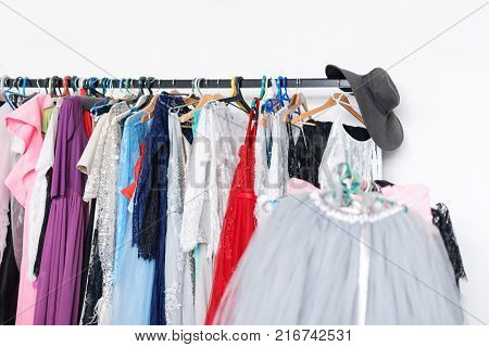 Many ladies evening gown long dresses on hanger in the dress rent shop for photo session. Dresses rental concept. Selective focus. Ball gown rental concept
