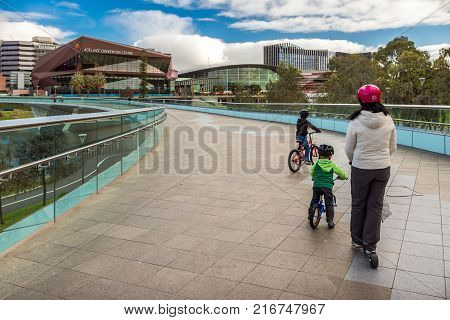 Adelaide Australia - August 27 2017: Mother with two sons ridind bicycles along Torrens footbridge in Adelaide city on a day