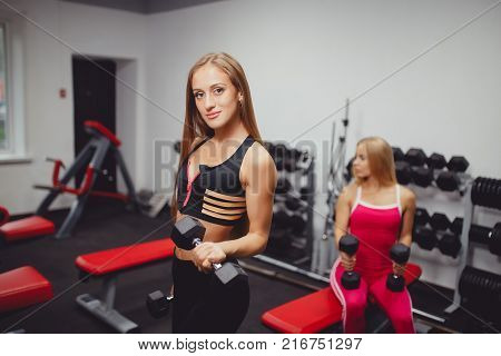 Dumbbells. Girls are engaged in a group, a body of body fitness with dumbbells. Elbow bending at the elbow