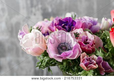 bouquet of mixed anemones flowers in vase . the work of the florist at a flower shop. Winter flower.