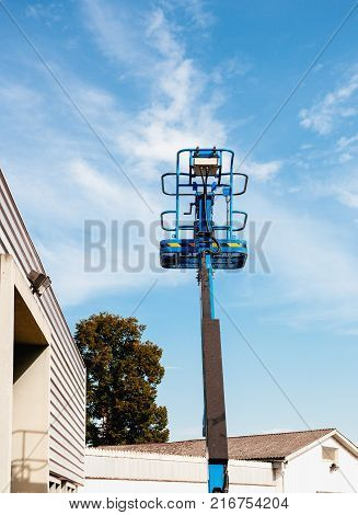 Blue Hydraulic Platform In Urban Enviroment With Blue Sky In The Background