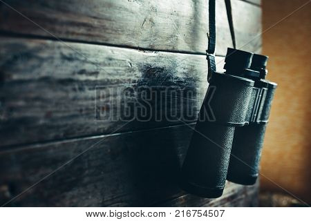 Accessories for travel Binocular Hanging On A Wooden Wall Copy Space With Left. Adventure Travel Scout Journey Concept