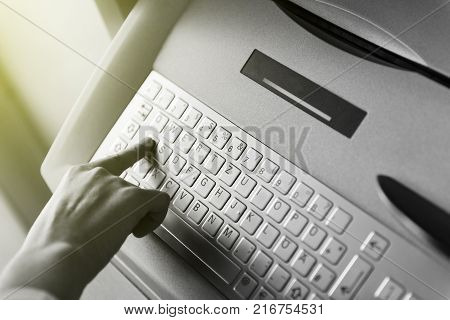 Modern Filter Over Woman Finger Pressing The A Letter Button On The Metallic Keyboard Of Atm Automat