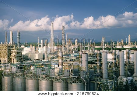 Petrochemical industry with distillation tower and smoke stack on blue sky background