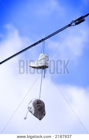 Old running shoes hanging on a hydro