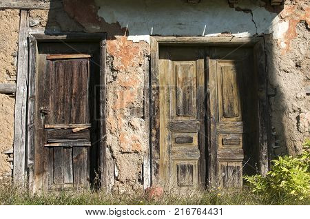 Old abandoned decayed grunge rural rickety house clay crumbled wooden weathered neglected doors