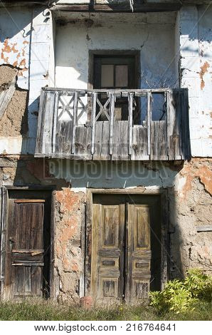 Old abandoned decayed grunge rural rickety house clay crumbled facade with neglected wooden window, balcony and doors