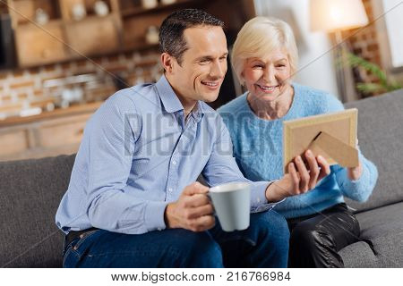 Sweet memories. Handsome young man sitting on the couch next to his elderly mother, drinking coffee and looking at the framed photo in his hands