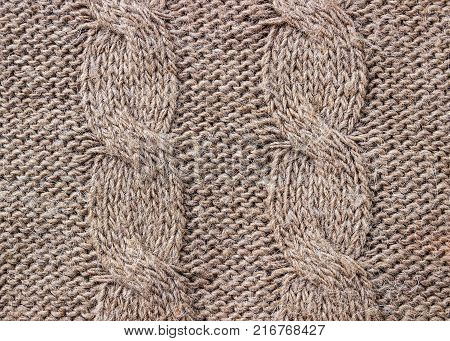 Knitted background. Knitted texture. A sample of knitting from wool. Knitting Pattern.