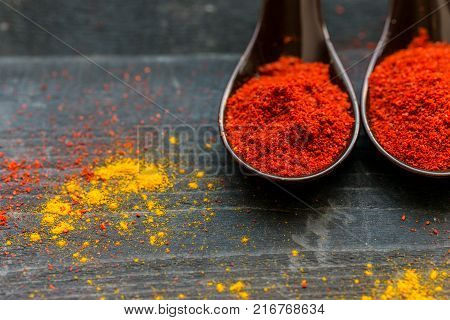 Top view of spoons filled with red paprika spice on dark wooden background covered with paprika and curry powder