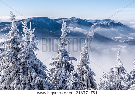 frozen winter Moravskoslezske Beskydy mountains panorama with Knehyne Velka Stolova and Radhost hill from Lysa hora hill during freezing day with clear sky