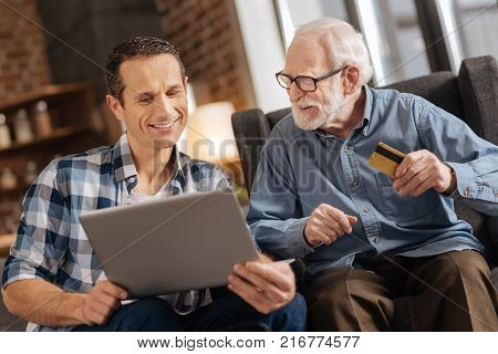 Fast and easy. Pleasant young man holding a laptop and showing an online shop webpage to his elderly father while the elderly man holding a bank card, ready to pay for purchases