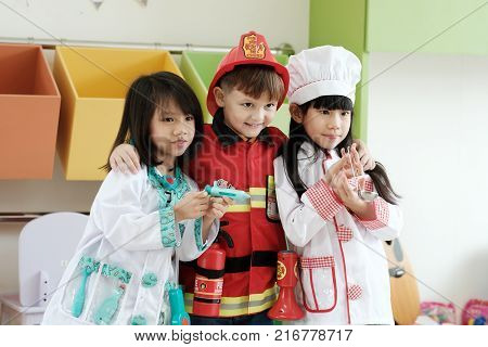 Cute boy and girls playing as fireman doctor and cook occupation in kindergarten class kid occupation education concept